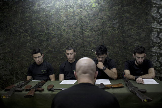 In this Tuesday, February 17, 2015 photo, Israeli high-school seniors are instructed on the AK-47 assault rifle as part of a privately run military combat fitness training as part of privately run military combat fitness training to prepare for national military service in Netanya, central Israel. (Photo by Oded Balilty/AP Photo)