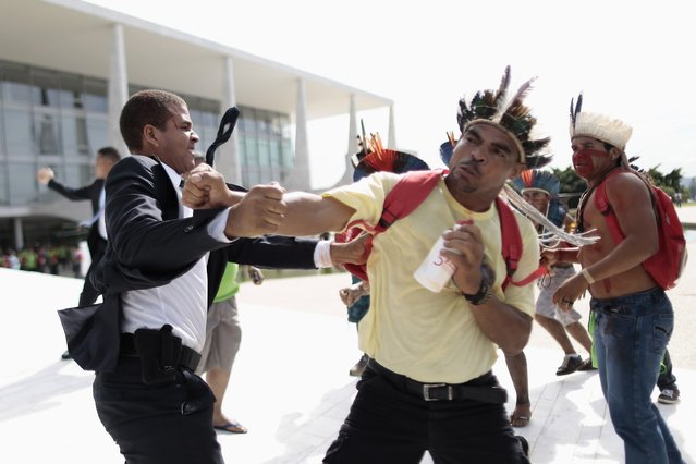 Indians clash with guards during a protest against the Indian policy of President Dilma Rousseff's government at the Planalto Palace in Brasilia, December 4, 2013. The protesters are opposing two bills being examined in National Congress, dealing with demarcation of indigenous lands, and demanding for the repeal of Ordinance 303 of the Attorney General of the Union (AGU). (Photo by Ueslei Marcelino/Reuters)