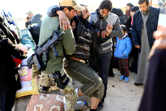 Iraqi rapid response forces help a wounded man, who fled the Islamic State stronghold of Mosul, in the Mithaq district of eastern Mosul, Iraq, January 3, 2017. (Photo by Thaier Al-Sudani/Reuters)