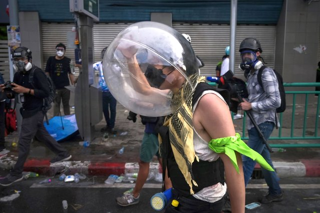 A protester wearing improvised protective headgear walks away from a cloud of tear gas on July 18, 2021 in Bangkok, Thailand. Student protesters called for a demonstration demanding the resignation of Thailand Prime Minister Prayuth Chan-o-Cha, despite a ban on gatherings because of the country's current Covid-19 outbreak, and folded a demand for better action in combating the virus into their demands. (Photo by Sirachai Arunrugstichai/Getty Images)