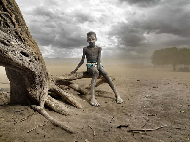 """""""Abore Sandstorm"""". This picture was taken in Omo Valley, Ethiopia. My guide and I reached an Arbore village and while we are speakng with the boss I looked to my right and i saw a brown tsunami coming to us. It was an incredible moment, women protecting of the storm with their cloths and I closed my eyes. (Photo and caption by Carlos Duarte (Spain)/2014 Sony World Photography Awards)"""