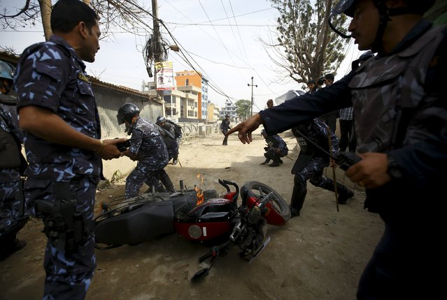 Riot police try to douse a motorcycle on fire after it was set alight by protesters during a nationwide strike, organised by the opposition alliance led by the Unified Communist Party of Nepal (Maoist) to demand the new constitution be drafted with the consensus of all political parties, in Kathmandu April 7, 2015. (Photo by Navesh Chitrakar/Reuters)