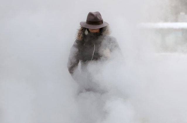 A woman walks through steam from an underground ventilation, as temperatures dropped below minus 20 degrees Centigrade ( minus 4 Fahrenheit) in Bucharest, Romania, Tuesday, January 10, 2017. Romania's Energy Minister Toma Petcu said neighboring Bulgaria had urgently asked for extra electricity, but the request was declined since the cold weather has stretched Romania's power grid and natural gas consumption in Romania could reach an all-time high due to the frigid temperatures. (Photo by Vadim Ghirda/AP Photo)