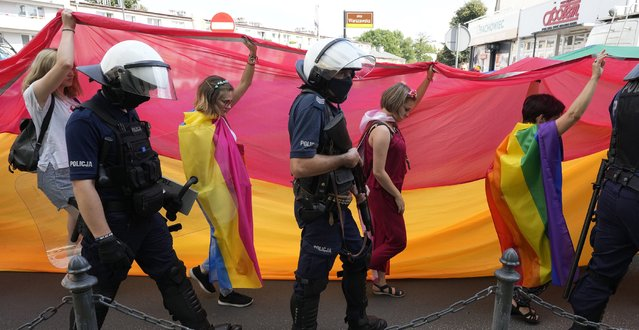 Participants in colorful 3rd Equality Parade march with rainbow flags under heavy police presence in support of LGBT rights at the foot of Poland's most revered Catholic shrine, the Jasna Gora Monastery in Czestochowa, Poland, Saturday, August 21, 2021. Under the massive police presence there were no clashes with a simultaneous small gathering of right-wing groups who held anti-LGBT rights banners. (Photo by Czarek Sokolowski/AP Photo)