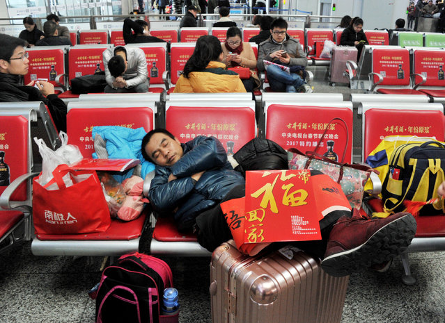 A passenger rests during the annual Spring Festival travel rush ahead of the Chinese Lunar New Year inside a railway station in Shanghai, China January 15, 2017. (Photo by Reuters/Stringer)