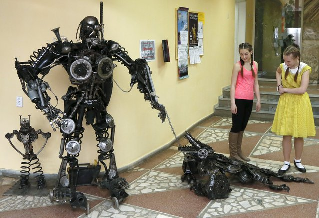 Girls look at a robot and a crocodile made from used car components, created by mechanic and welder Sergei Kulagin, at his exhibition in Russia's Siberian city of Krasnoyarsk April 11, 2015. Kulagin, who is an amateur artist, has created about one hundred sculptures made from used car parts in his free time and his exhibition opens on April 13, according to organisers. (Photo by Ilya Naymushin/Reuters)