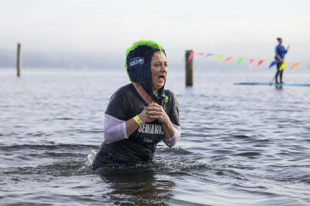 A woman reacts after entering Lake Washington during the 12th annual Polar Bear Plunge in Seattle, Washington January 1, 2014. Hundreds participated in the chilly New Year's Day tradition, organized by Seattle Parks and Recreation and held at Matthews Beach. (Photo by David Ryder/Reuters)