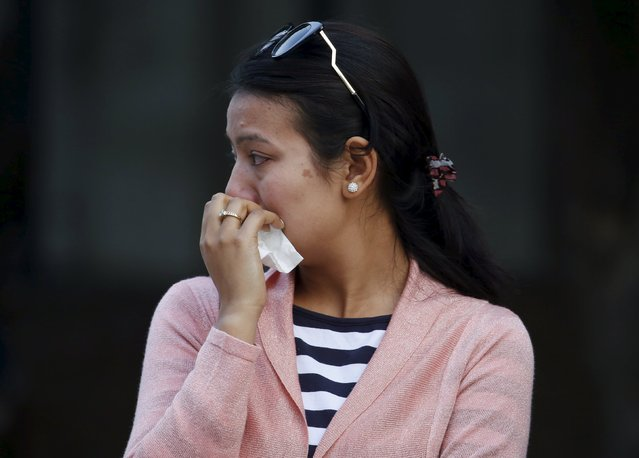 A family member cries as the bodies of crew members of a Twin Otter plane, operated by private Tara Air, that crashed on Wednesday are taken for post-mortem at a teaching hospital in Kathmandu, Nepal, February 25, 2016. (Photo by Navesh Chitrakar/Reuters)