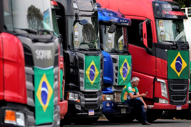 A truck driver sits amid trucks parked at a camp set up by supporters of President Jair Bolsonaro in Brasilia, Brazil, Monday, September 6, 2021. People are arriving to the capital to show their support for the president at the next day's Independence Day events. (Photo by Eraldo Peres/AP Photo)