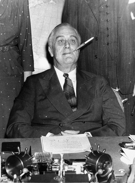 """In this March 4, 1943 file photo, President Franklin D. Roosevelt poses for photographers with a cigarette in his mouth as he started his 11th year in the White House. He said, """"Let's make one this way, boys"""". (Photo by AP Photo)"""