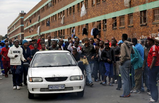 Locals harass a motorist who was driving past a hostel during the anti-immigrant violence in Johannesburg, April 17, 2015. (Photo by Siphiwe Sibeko/Reuters)