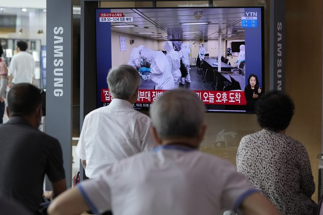 """People watch a TV showing an image of South Korean service members wearing protective clothes disinfect inside the naval destroyer Munmu the Great during a news program at the Seoul Railway Station in Seoul, South Korea, Tuesday, July 20, 2021. South Korea's prime minister on Tuesday apologized for """"failing to carefully take care of the health"""" of hundreds of sailors who contracted the coronavirus on a navy ship taking part in an anti-piracy mission off East Africa. (Photo by Ahn Young-joon/AP Photo)"""
