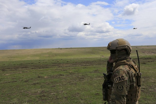 "A British soldier looks on as U.S. military helicopters fly during the ""Wind Spring 15"" military exercises at Smardan shooting range April 21, 2015. (Photo by Radu Sigheti/Reuters)"