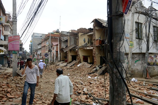 Nepalese people walk past collapsed buildings at Lalitpur, on the outskirts of Kathmandu on April 25, 2015.  A powerful 7.9 magnitude earthquake struck Nepal, causing massive damage in the capital Kathmandu with strong tremors felt across neighbouring countries. (Photo by Prakash Mathema/AFP Photo)