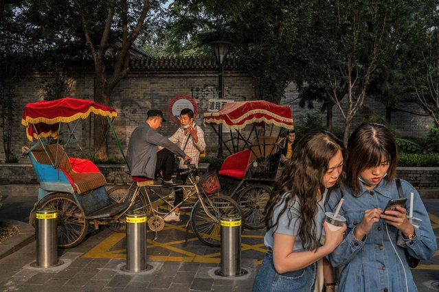 Bicycle rickshaw drivers chat as they wait for customers near the Drum Tower in a traditional neighbourhood on September 30, 2021 in Beijing, China. China will mark National Day and the Golden Week holiday from October 1st. (Photo by Kevin Frayer/Getty Images)