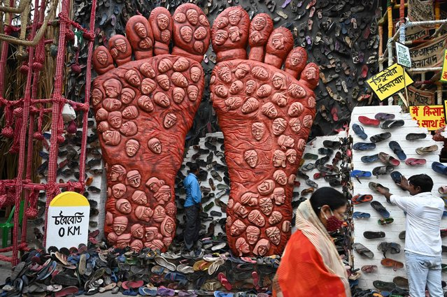 A person walk past workers decorating of a makeshift place of worship for Durga Puja with a theme in support the ongoing farmers protest against the central government's agricultural reforms, in Kolkata on October 6, 2021. (Photo by Dibyangshu Sarkar/AFP Photo)