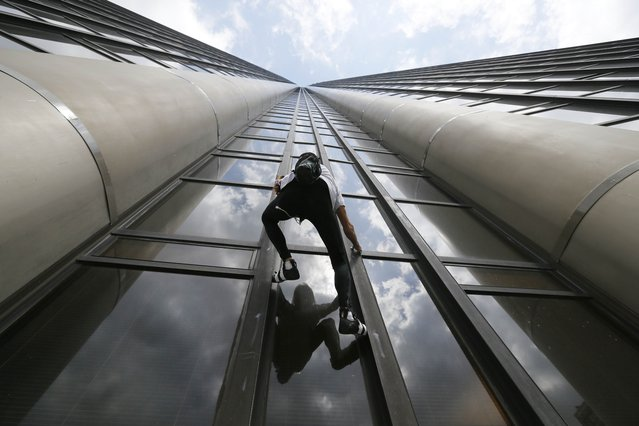 "French climber Alain Robert, also known as ""Spiderman"", is reflected in a glass plane window as he scales the Tour Montparnasse, a 210-metre (689 ft) building in central Paris, France April 28, 2015, where he carried a Nepal flag in tribute to the victims of the recent earthquake. (Photo by Gonzalo Fuentes/Reuters)"