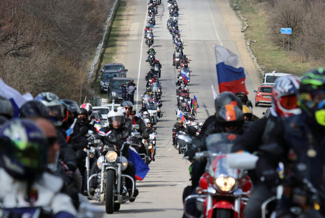"""Bikers, including members of the motorcycling club """"Night Wolves"""", ride before a festive event marking the fifth anniversary of Russia's annexation of Crimea on Mount Gasforta in Sevastopol, Crimea March 16, 2019. (Photo by Alexey Pavlishak/Reuters)"""