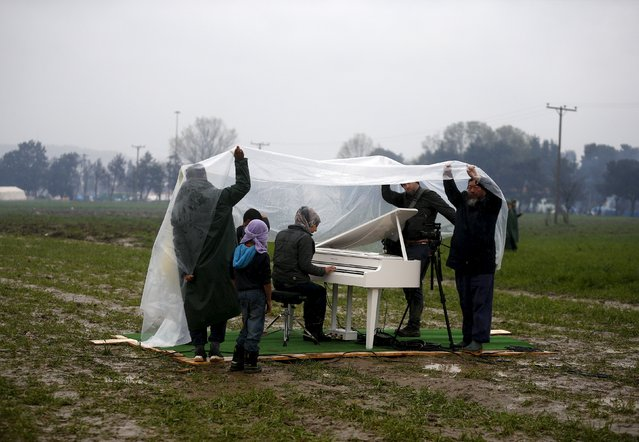 Chinese dissident artist Ai Weiwei (R) holds a rain cover to protect a Syrian refugee woman from the rain, as she performs in a field, on a piano brought by the artist, near a makeshift camp on the Greek-Macedonian border, near the village of Idomeni, Greece March 12, 2016. (Photo by Stoyan Nenov/Reuters)