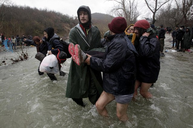 Refugees and migrants attempt to cross a river near the Greek-Macedonian border to enter Macedonia after an unsuccessful attempt yesterday, west of the village of Idomeni, Greece, March 15, 2016. Hundreds of migrants have managed to breach the Greek-Macedonian border, further along from where the main crossing is closed. As many attempted to get across a swollen river, tragedy struck: Macedonian police say two men and a woman drowned. Photo by Alexandros Avramidis/Reuters)
