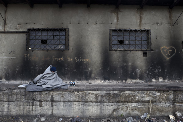 An Afghan refugee man wraps himself with a blanket to shield from the morning cold while sitting outside an abandoned warehouse where he and other refugees took refuge in Belgrade, Serbia, Monday, February 6, 2017. Hundreds of migrants have been sleeping rough in freezing conditions in central Belgrade looking for ways to cross the heavily guarded EU borders. (Photo by Muhammed Muheisen/AP Photo)