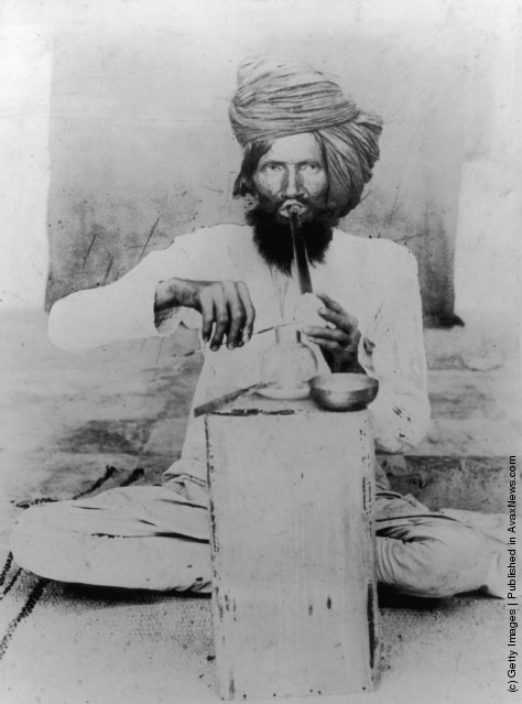 circa 1900:  A man in a turban sits cross-legged smoking opium in Meywar, Rajputana