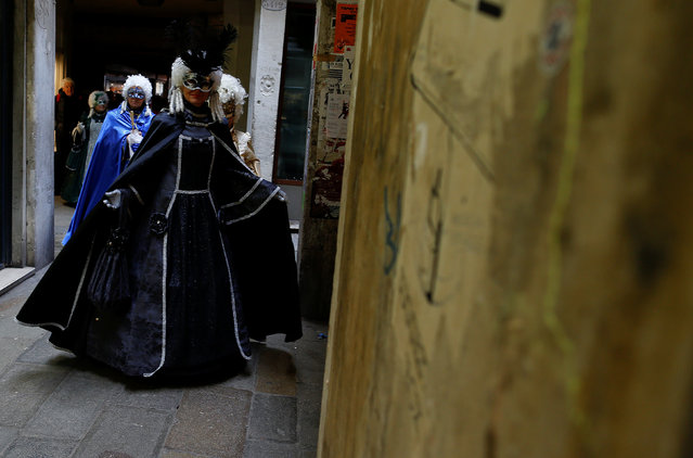 Masked revellers walk along a street during the Venice Carnival in Venice, Italy February 11, 2017. (Photo by Tony Gentile/Reuters)