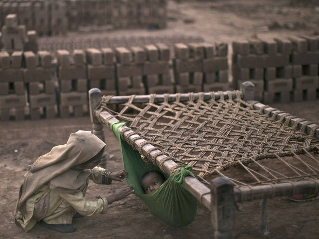 Pakistani girl, Kiran Riasat, 8, who works with her mother and father, seen in the background, in a brick factory, checks on her brother, Rizwan, 1.5, laying in a hammock attached on a bed, at the site of work, in the outskirts of Islamabad, Pakistan, Tuesday, February 18, 2014. According to Kiran's parents she started to work at the factory 3 years ago, and they couldn't afford financially sending her to a school. (Photo by Muhammed Muheisen/AP Photo)
