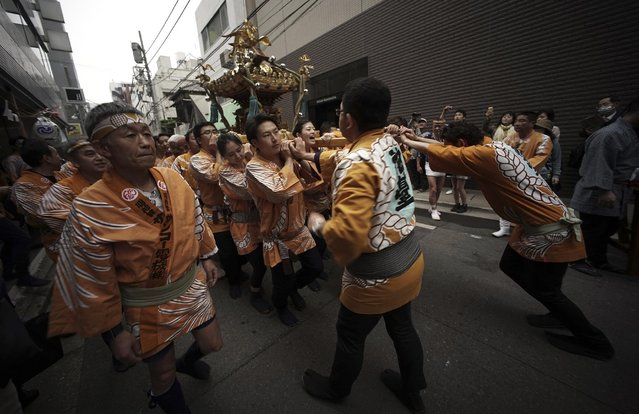 Carrying a portable shrine, on their shoulders, participants all clad in traditional happi coats, parade through precincts of the Kanda Myojin shrine during the annual summer festival in Tokyo, Saturday, May 9, 2015. (Photo by Eugene Hoshiko/AP Photo)