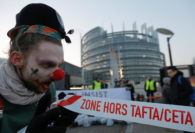 """A demonstrator dressed as a clown holds a banner with the words """"TAFTA/CETA FREE ZONE"""" as he takes part in a protest against the Comprehensive Economic Trade Agreement (CETA) between the EU and Canada, in front of the European Parliament in Strasbourg, France, February 15, 2017. (Photo by Vincent Kessler/Reuters)"""