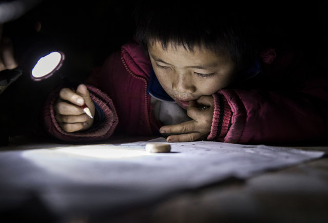 """""""Left behind"""" child Luo Hongniu, 8, does homework by flashlight at the family's home on December 15, 2016 in Anshun, China. (Photo by Kevin Frayer/Getty Images)"""