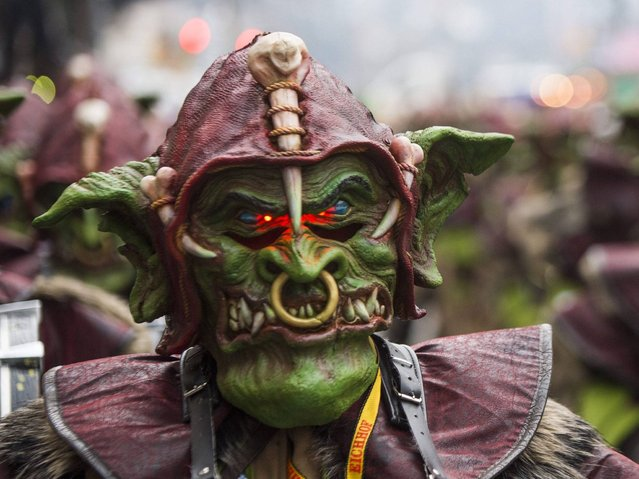 A participant wears a scary mask as he arrives to take part in a procession through the historic centre of Lucerne. (Photo by Sigi Tischler/Keystone)