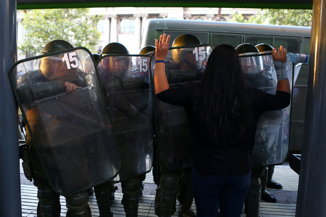 A woman raises her arms in front of riot policemen during a rally marking the anniversary of the death of union leader Juan Pablo Jimenez, in Santiago, Chile February 21, 2017. (Photo by Ivan Alvarado/Reuters)