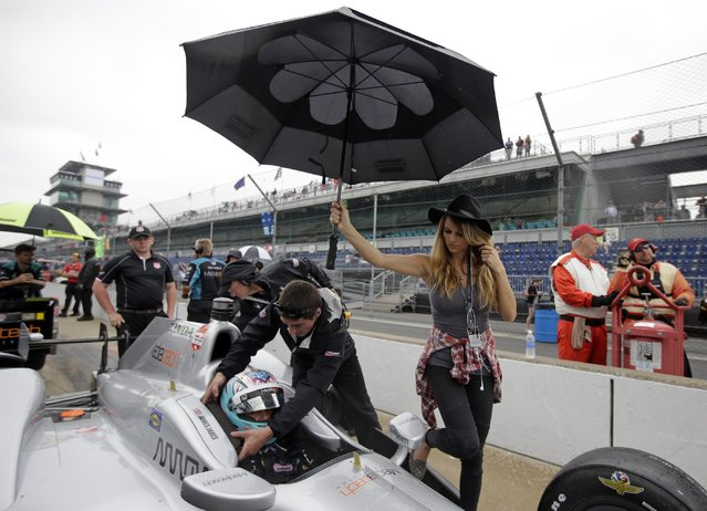 A crewman assists James Jakes, of England, out of the car under an umbrella held by Meghan Williams as rain halted qualifications on the first day of qualifications for the Indianapolis 500 auto race at Indianapolis Motor Speedway in Indianapolis, Saturday, May 16, 2015. (Photo by Darron Cummings/AP Photo)