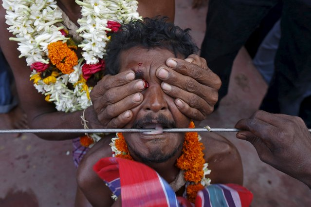 The tongue of a Hindu devotee is pieced with a metal skewer during the annual Shiva Gajan religious festival in Banga village in West Bengal, India, April 13, 2016. (Photo by Rupak De Chowdhuri/Reuters)