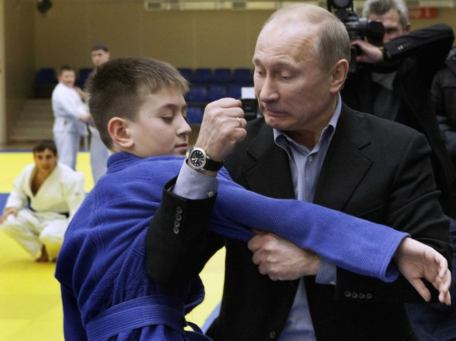 Vladimir Putin shows a hold to a young judo wrestler at the Regional Judo Center at the Arena Sports Complex in the Siberian city of Kemerovo on January 24, 2012, during his visit to the region. Putin is known for his passion for judo, in which he has a black belt. (Photo by AFP Photo/STR)