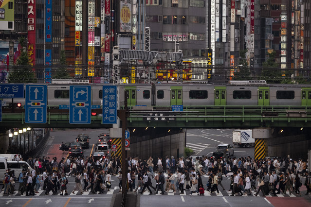 A large crowd passes a pedestrian crossing as a commuter train travels overhead Monday, May 27, 2019, in the Shinjuku district of Tokyo. (Photo by Jae C. Hong/AP Photo)