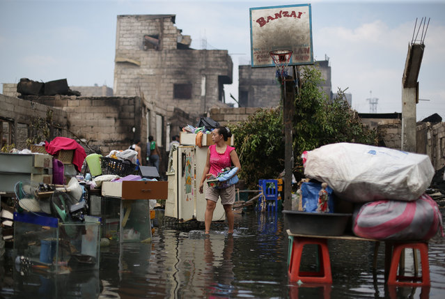 A Filipino woman searches for belongings along a flooded road beside their burned house in Manila, Philippines, Sunday, March 23, 2014. About 200 houses were gutted by fire as authorities are still investigating the cause of the fire. (Photo by Aaron Favila/AP Photo)