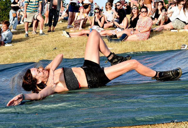 Festival goers ride a makeshift slip and slide during day two of Glastonbury Festival at Worthy Farm, Pilton on June 27, 2019 in Glastonbury, England. (Photo by Shirlaine Forrest/WireImage)
