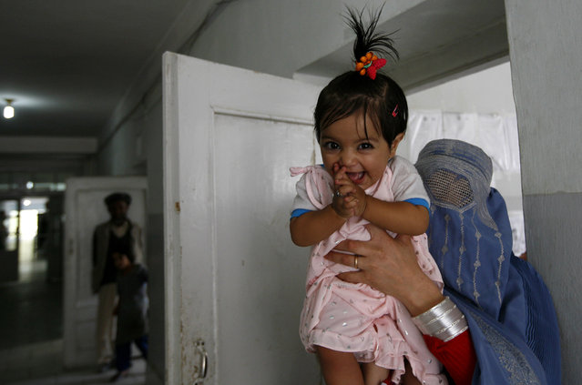 An Afghan girl reacts as she arrives with her mother for treatment in the local hospital of Feyzabad, on September 28, 2008. (Photo by Anja Niedringhaus/AP Photo)