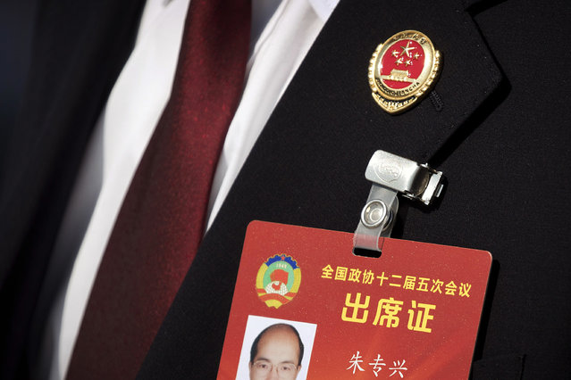 In this Friday, March 10, 2017 photo, a member of China's procuratorate wears a pin on his lapel as he arrives to hear a report by the head of China's Supreme People's Procuratorate during a plenary session of the Chinese People's Political Consultative Congress (CPPCC) in Beijing. (Photo by Mark Schiefelbein/AP Photo)