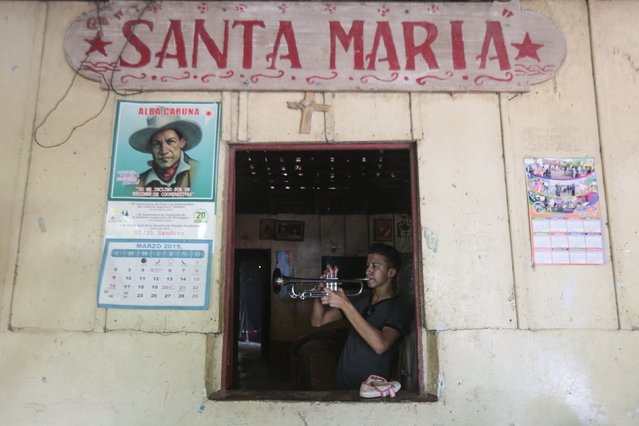 A young man plays a trumpet during celebrations in honour of San Juan Bautista in San Juan de Oriente town, Nicaragua, June 26, 2015. (Photo by Oswaldo Rivas/Reuters)