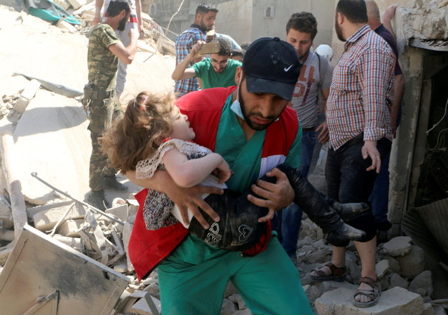 A civil defence member carries a child that survived from under the rubble at a site hit by airstrikes in the rebel held area of Old Aleppo, Syria, April 28, 2016. (Photo by Abdalrhman Ismail/Reuters)