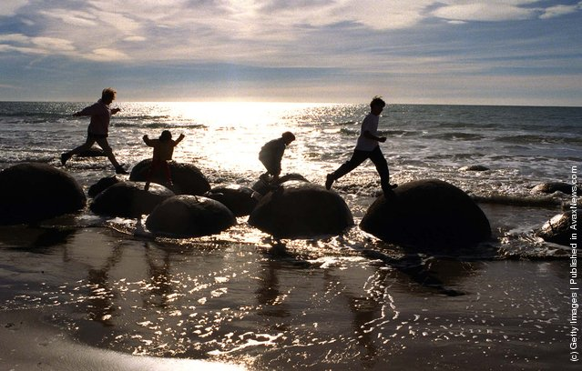 Making the most of the warm autumn morning sunshine, the Devcich family of Winton, Southland, play on the Moeraki boulders on the east coast, north of Dunedin, 1998