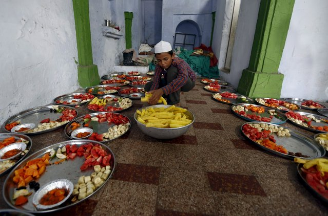 A Muslim boy prepares plates of food for an Iftar (breaking of fast) meal inside a mosque during the holy month of Ramadan in Ahmedabad, India, June 28, 2015. (Photo by Amit Dave/Reuters)