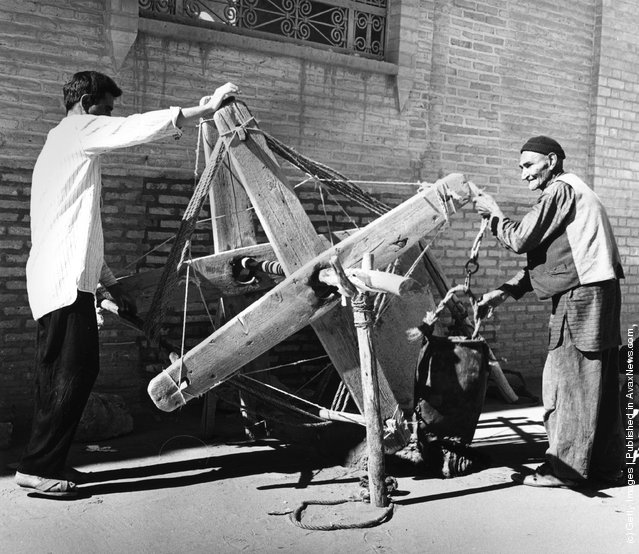 1955:  A well is dug in Yazd, Iran, using a wooden windlass and leather bag. Many of the methods and construction techniques used in Iran have not changed in a thousand years