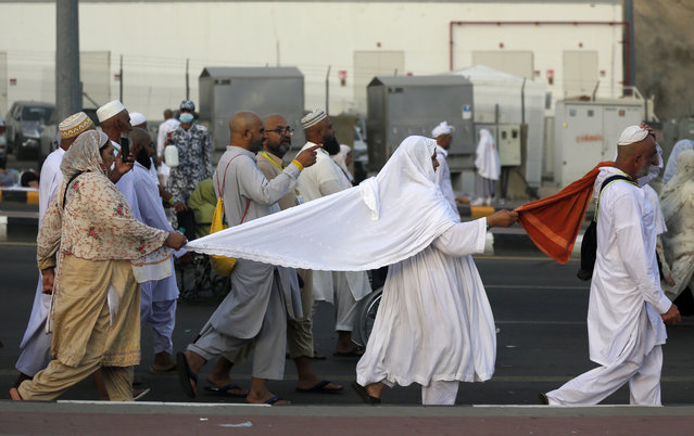 Pakistani Muslim pilgrims hold to each other to avoid being separated as they walk to cast stones at a pillar in the symbolic stoning of the devil, the last rite of the annual hajj, on the second day of Eid al-Adha, in Mina near the holy city of Mecca, Saudi Arabia, Monday, August 12, 2019. The pilgrimage to Mecca is required once in a lifetime of every Muslim who can afford it and is physically able to make it. (Photo by Amr Nabil/AP Photo)
