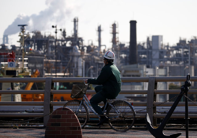 A worker cycles near a factory at the Keihin industrial zone in Kawasaki, Japan February 28, 2017. (Photo by Issei Kato/Reuters)