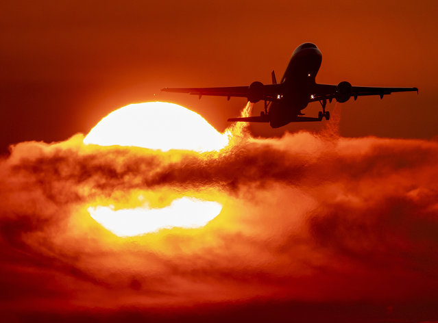 An aircraft passes the rising sun during take off at the international airport in Frankfurt, Germany, Monday, September 2, 2019. (Photo by Michael Probst/AP Photo)