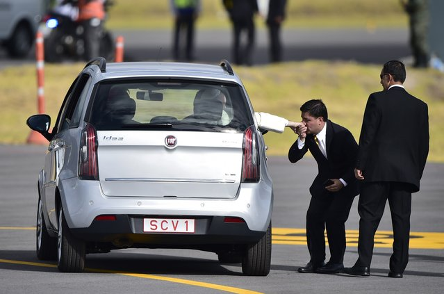 A man kisses Pope Francis's ring as he leaves aboard a small car the Mariscal Sucre international airport in Quito on July 5, 2015. Pope Francis arrived in Quito Sunday to begin his first South American trip in two years, for an eight-day tour of Ecuador, Bolivia and Paraguay highlighting the plight of the poor on his home continent. (Photo by Rodrigo Buendia/AFP Photo)
